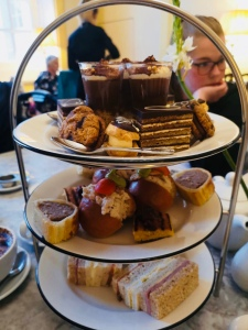 High Tea. Three tier cake stand. Sandwiches on the bottom. A brioche roll, sausage roll and mini cheese toastie on the middle tier. Chocolate desserts on the top tier.