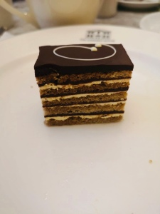 A slice of signature gateau on a white plate. The gateau is made from many thin layers of sponge, cream and chocolate