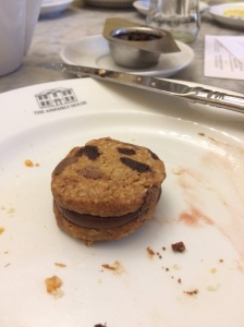 Chocolate chip cookie sandwich with chocolate cream in the centre. On a white plate with crumbs and food stains. You can see a Tea strainer in the distance