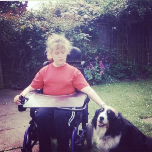 A photo of me aged around 11 years old. I am in my wheelchair and have frizzy hair!
