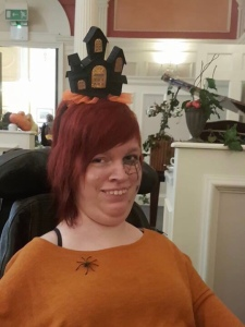 I am wearing orange and black. I have a plastic spider on my shoulder and a black and orange light up house style hat.