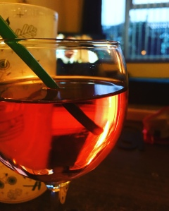 A glass of rosé wine with a straw. You photo is taken in candlelight and the wine is glowing.