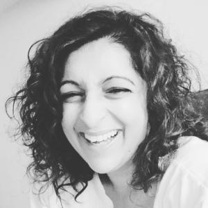 Portrait photo of Ritu smiling. In black and white.