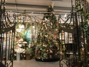 Ironwork gates leading to a magnificent Christmas tree in the garden centre. There are lights and gold decorations