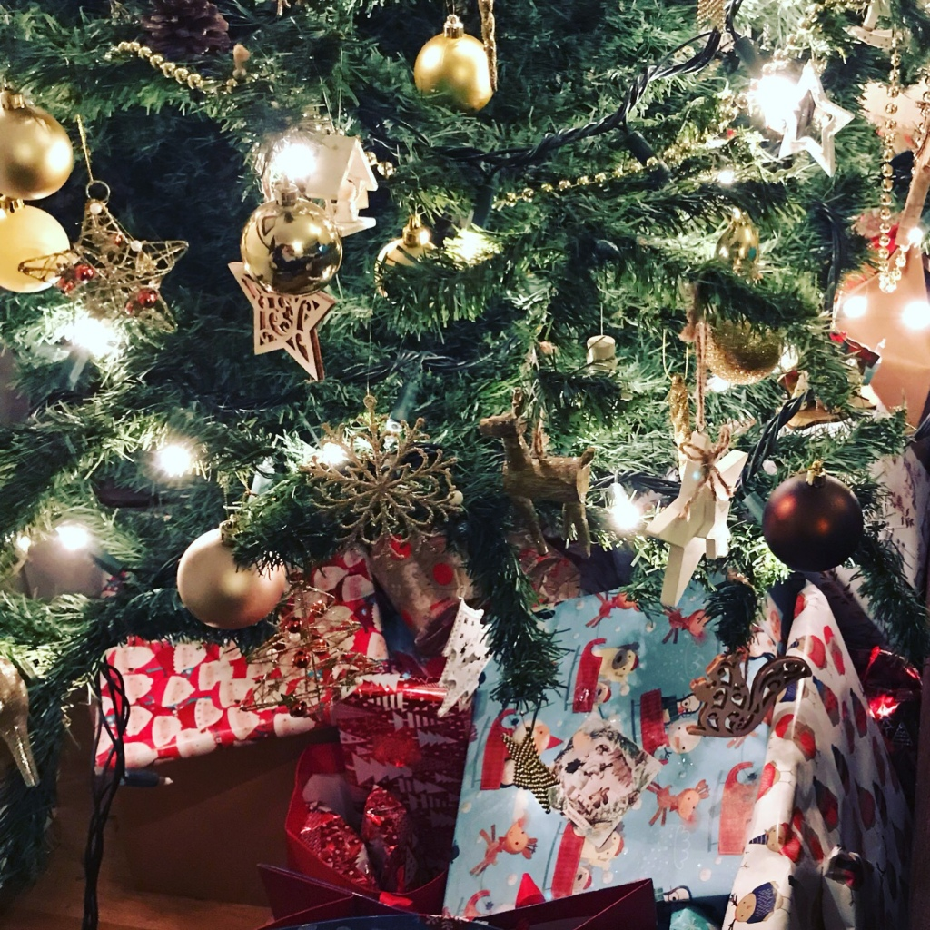 Close up photo of gifts under a Christmas tree