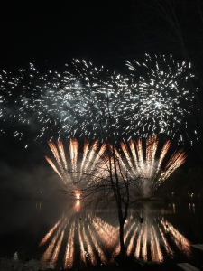 A mirror image of red fireworks in the sky and on the water of the lake.