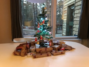 A mini Christmas tree on the white dining room table. There are small gifts wrapped up under the tree. The window behind looks out onto trees and a pathway.