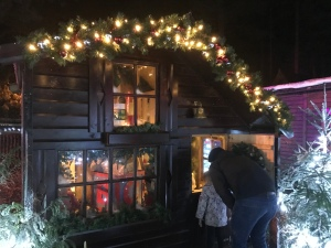 A small wooden cabin with lights outside. Somebody standing peering inside