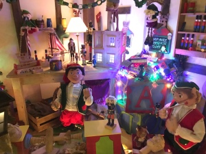 A workshop full of elves working away at preparing gifts. In the background there is a desk and shelves with toy soldiers on.