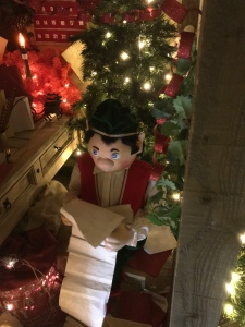 A model elf reading a long scroll of paper. A Christmas tree and candle in the background.