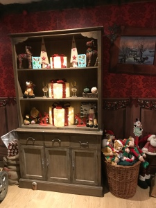 A large bookcase filled with books a decorations. A basket full of gifts. The wallpaper is red.