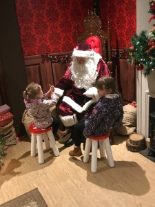 Father Christmas sitting on a grand wooden throne, talking to my nieces. There is a fireplace on the right.