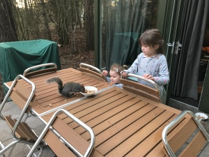 Outside on the patio table my nieces are sharing breakfast with a friendly squirrel. It is very close to them.