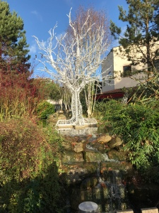 A night sunny photo of the light tree sculpture. It is reflected in the stream below.