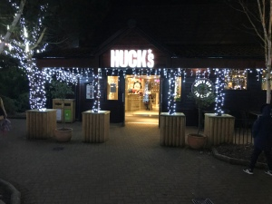 The entrance to Hucks restaurant lit up at night.