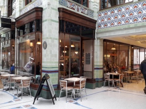 A photo taken outside Marmalades café yet still inside Royal Arcade. There is seating outside the café. Big windows give you a glimpse inside. There is Art Nouveau tile work on the architecture.