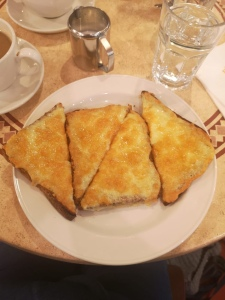 This photo is taken looking down on to a plate of cheese on toast. There are two slices of toast, each cut in half. Arranged attractively in triangles.