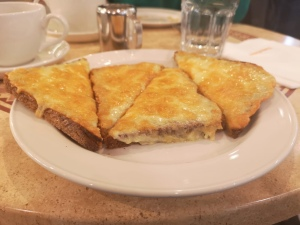 The same plate of cheese on toast. Photo taken from a side angle. Cheese is melting over the edges of the toast.