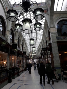 Looking down the long shopping area of Royal Arcade Norwich. There is a curved glass roof, and black metalwork ornate light fittings hanging down like lamps.