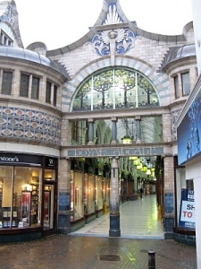 Large archway leading inside Royal Arcade. Stone column and decorative tile work in blues and greys.