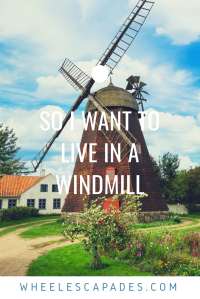 A bright colourful image of a windmill on green grass with a tree and blue sky. The title text So I Want To Live In A Windmill is placed over. This is an image to pin for my accessible housing post.