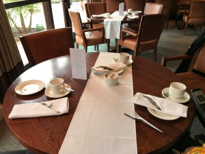 A photo taken looking down onto the large round table. There are plates at napkins at the place settings and a large window in the background.