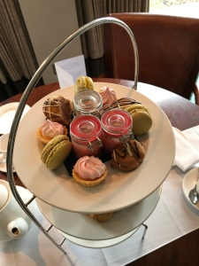 Looking down on to the top tier of desserts. There are three tarts, three macarons, three halves of choux bun and three small jars filled with pink posset.