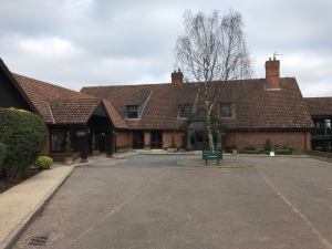 A photo taken wheeling towards the main entrance at Barnham Broom Country Club. It is a long l shaped brick building. The sky is grey with clouds.