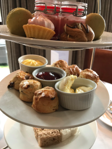 A close up of the afternoon tea stand, focussing on the scones. There a six mini scones with pots of cream, jam and butter.