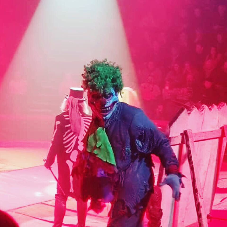 Close up shot of a scary clown coming towards me. The clown has a white face, red nose and green hair. Pulling a scary face.