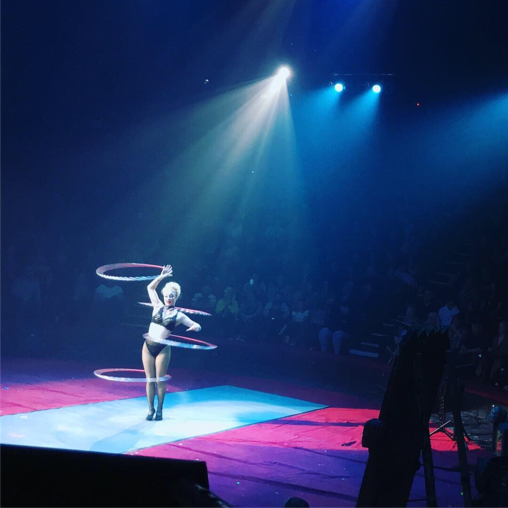 A lady with short white hair and a black bikini style clothing is hula hooping with multiple hoops on her body and arm.