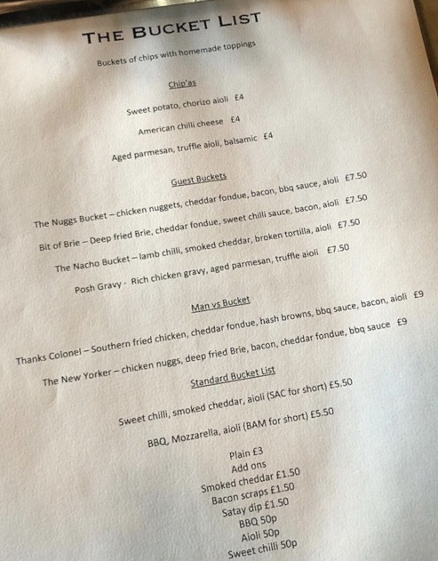 A photograph of the current menu. It includes the buckets we ordered at £7.50 as described below. Along with sweet potato chips and various sauces.