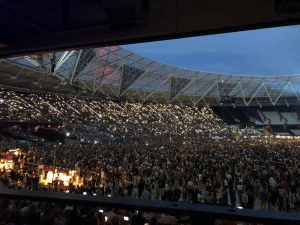 The audience is lit up by a sea of mobile phone screens and torches.