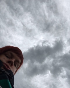 Me looking down into the camera with the camera facing a dark and cloudy sky