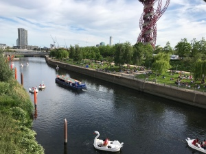 The view of the river from the bridge. There are swan shaped boats with people on in the river. Greenery lines both sides of the river. A tower block style building is in the distance along with the red sculpture to the right