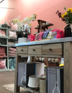 Inside the gift shop area, the walls are a dusty pink, there is a rustic looking table with drawers, on it sit a selection of things to buy, behind and cushions for sale