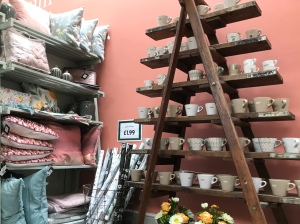 Wooden shelving displays various cups and mugs that are for sale. Patterned cushions are displayed to the left