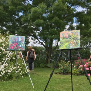 Two artist easels with paintings on canvas standing in the gardens.