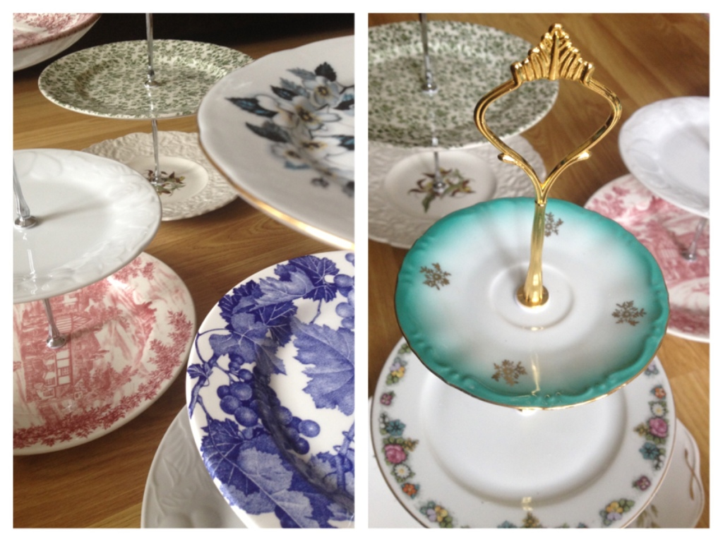 A group of cake stands with three tiers of mis-match plates in contrasting colours and patterns. The plates are of an old style and mostly floral.