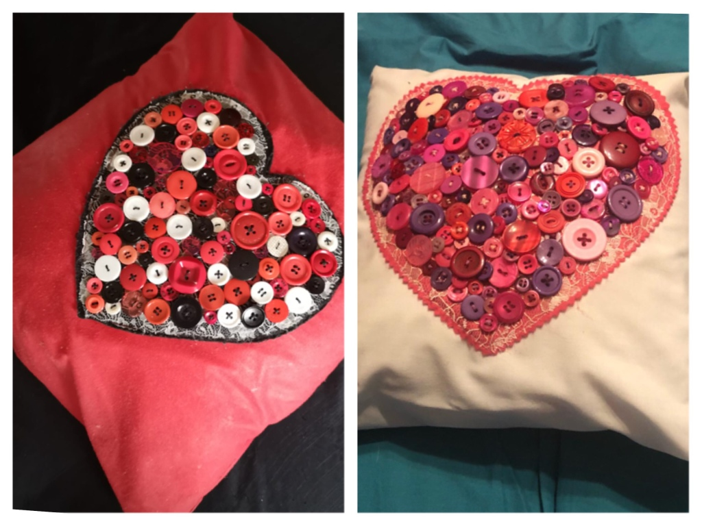 Two cushions decorated with lots of buttons sewn to form the shape of a heart. The are layered onto a large felt heard before being sewn on to the cushion. The cushion on the left is red black and white. The one on the right is pinks purples and reds.