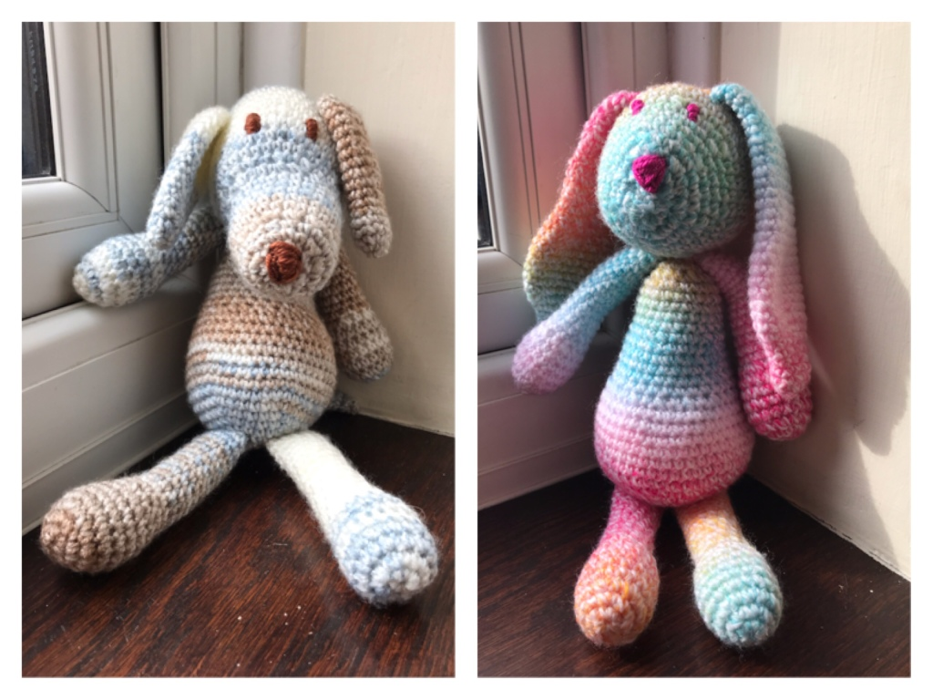 On the left is a stuffed crochet dog in blue brown and white graduated wool. On the right is a crochet bunny using multicoloured rainbow stripy wool. It has big long ears.