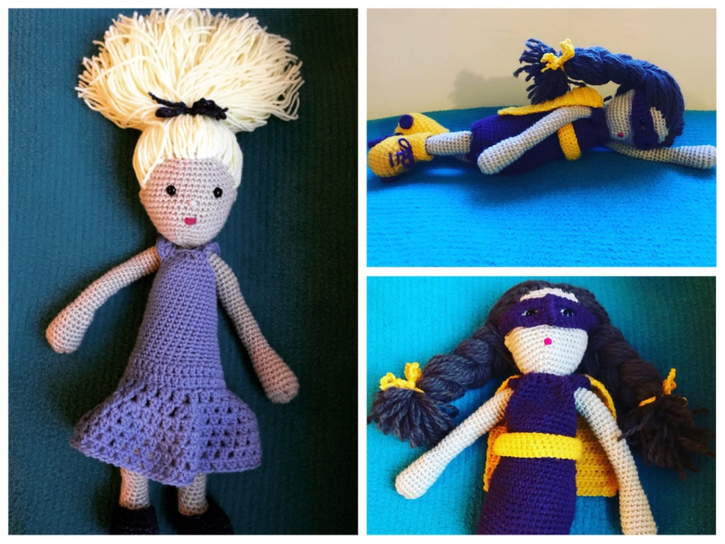 These are crochet dolls. Atomic blonde on the left has masses of long light yellow hair tied in a ponytail on top of her head. She is wearing a pale purple dress that looks lacy and long. On the right is Super Girl, she is wearing a purple eye mask and yellow cape. Her dark brown hair is plaited in pigtails. She has yellow roller skates with purple laces.