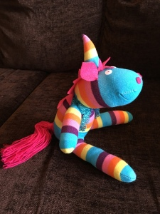 Photo of the sock unicorn taken from the side. He is stuffed and sitting up. He has a pink wool tail and pink ears.