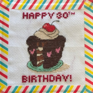 A cross stitch design chocolate cake with a slice removed. The cake has a cherry on top and the words Happy 30th Birthday are cross stitched. There is a stripy rainbow coloured boarder made with washi tape.