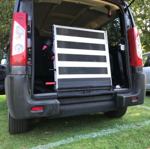 The back of my wheelchair accessible van with the ramp up and the back door open. It is parked on grass.