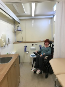 Me in the right hand corner of the spacious accessible toilet. There is also a height adjustable bed, and a sink