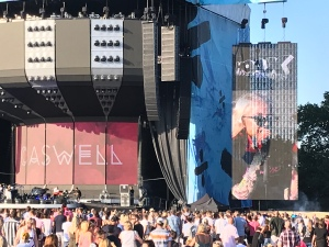 Caswell are on stage. On the screen to the right of the stage is the female lead singer. The backdrop to the stage is red with Caswell written on.