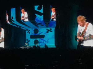 Ed Sheeran is on stage. It's blue, with the Divide logo as the backdrop, and he can be seen on the large screens.