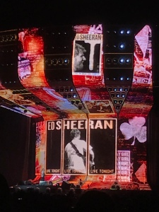 Photographs and clips of Ed Sheeran are the backdrop of the stage as he sings.