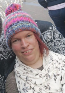 A headshot of myself, selfie style. I am wearing a stripy rainbow multicoloured knitted hat, and a cream coloured scarf with small birds printed on.